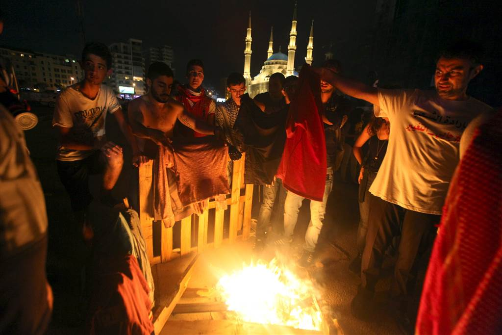 Protesters warm themselves and dry their clothes over a fire after being sprayed by water cannons in Martyr square, downtown Beirut. (Stringer/Reuters)