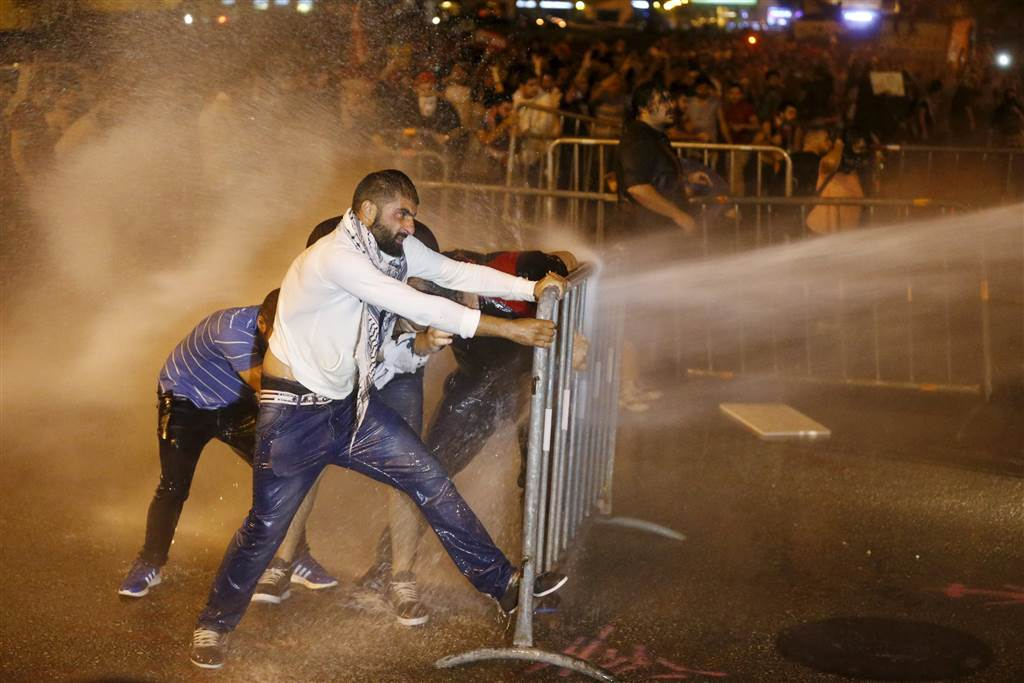 Protesters hold on to a barricade while being sprayed with water from water cannons. (Mohamed Azakir/Reuters)
