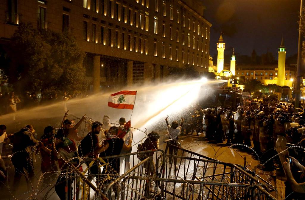 Lebanese protesters are sprayed with water. (Mohamed Azakir/Reuters)