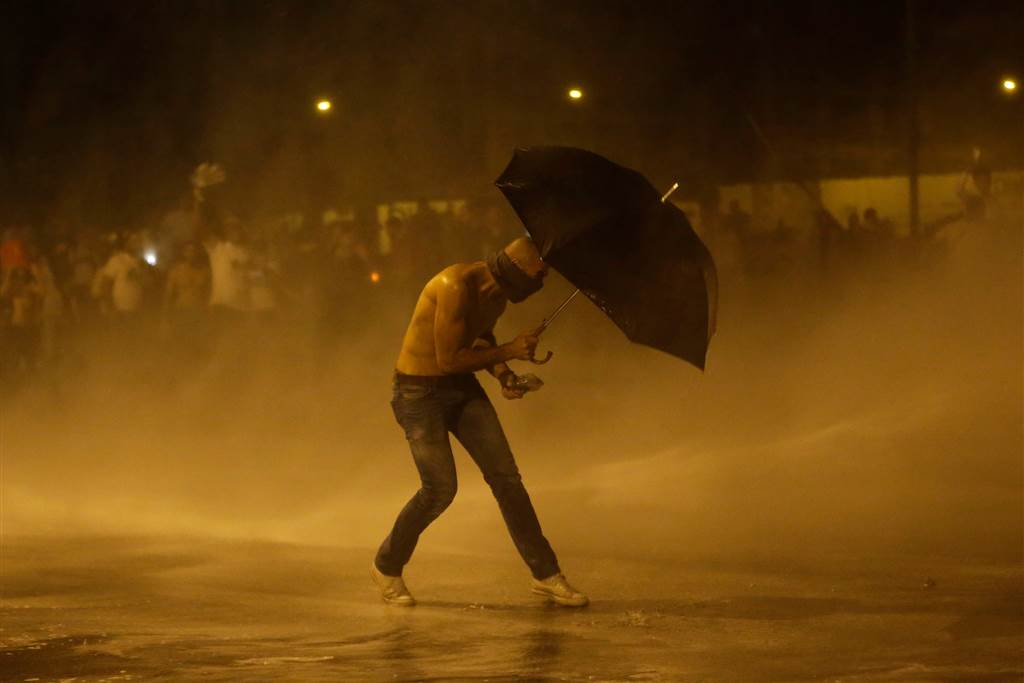 A protester holds an umbrella as he is sprayed by water cannons. (Hassan Ammar/AP)