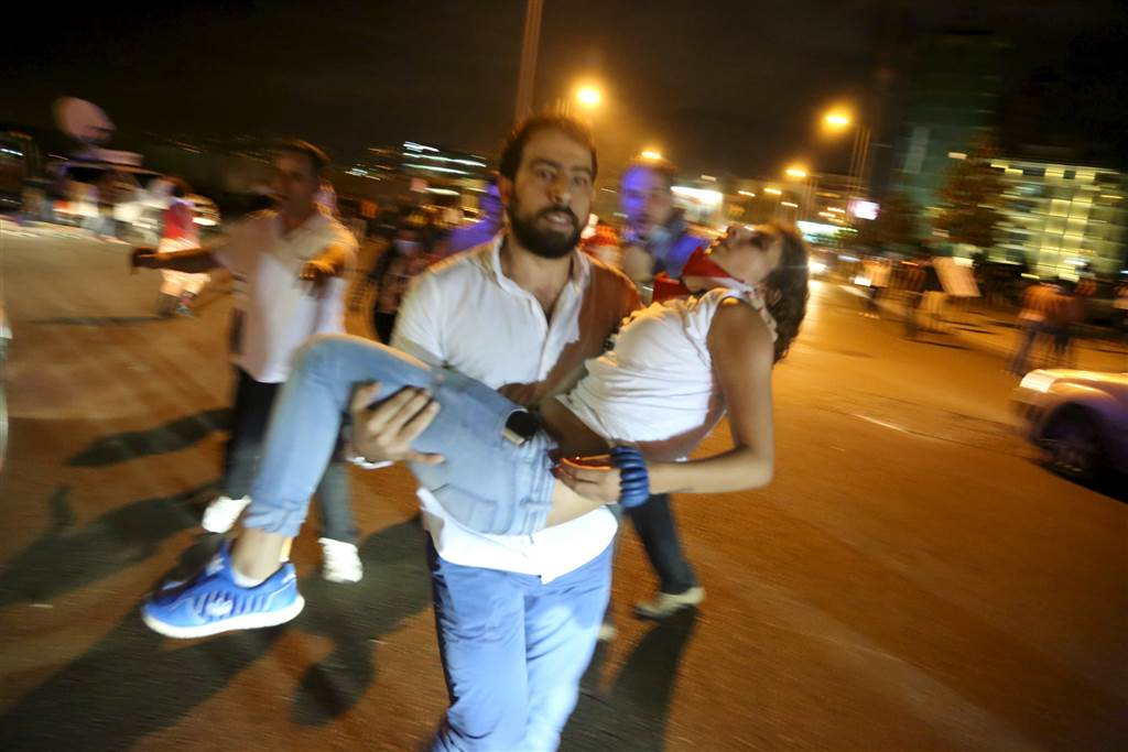 A man carries a protester affected by tear gas. (Aziz Taher/Reuters)