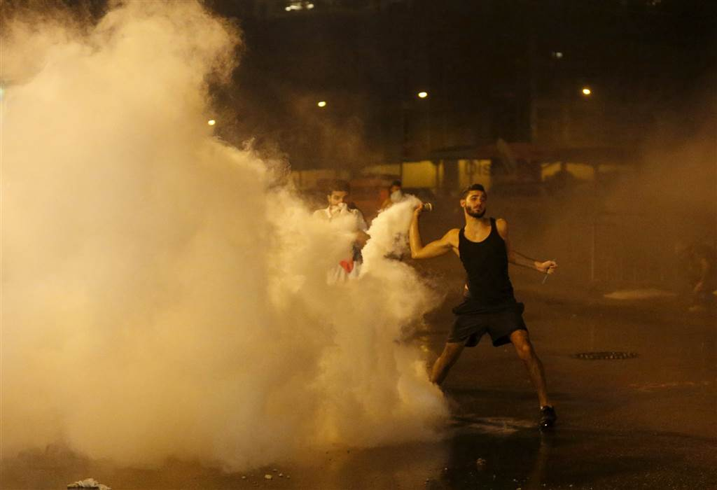 A protestor throws back a tear gas canister. (Mohamed Azakir/Reuters)