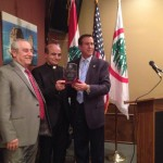 Lebanese Forces USA Coordinator Maurice Daaboul and Detroit Chapter President Tony Malouf present Bishop A. Elias Zaidan with an honorary plaque.